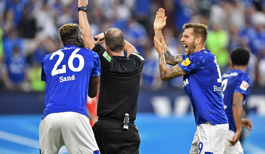 FILE -- In this Saturday, Aug. 24, 2019 photo Schalke's Guido Burgstaller, right, complains to referee Marco Fritz during the German Bundesliga soccer match between FC Schalke 04 and Bayern Munich in Gelsenkirchen, Germany. Newly implemented handball rules are stoking renewed criticism for the video assistant referee in the Bundesliga. (AP Photo/Martin Meissner, file)