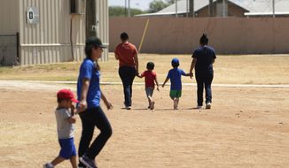 In this file photo, immigrants seeking asylum hold hands as they walk across the ICE South Texas Family Residential Center, Friday, Aug. 23, 2019, in Dilley, Texas. The South Texas facility is just at 6% capacity, according to ICE documents released in August 2020. The agency told a federal court on August 24, 2020 that thus far there have been no COVID-19 breakouts at South Texas or the other two family-detention facilities it runs. (AP Photo/Eric Gay) ** FILE **