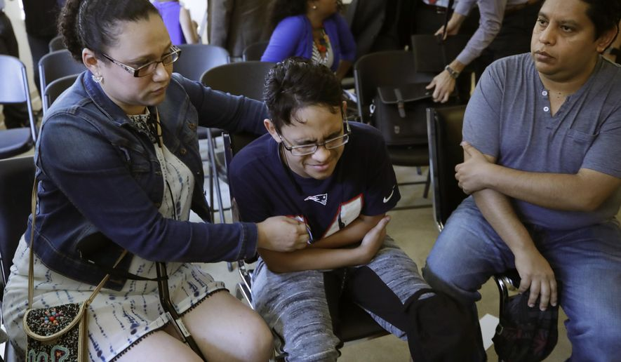 Gary Sanchez, of Honduras, right, watches as his wife, Mariela comforts their son, Jonathan, 16, during a news conference, Monday, Aug. 26, 2019, in Boston. The Sanchez family came to the United States seeking treatment for Jonathan's cystic fibrosis. Doctors and immigrant advocates say federal immigration authorities are unfairly ordering foreign-born children granted deferred action for medical treatment to return to their countries. (AP Photo/Elise Amendola) **FILE**