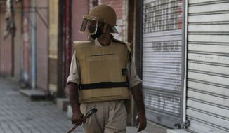 In this Thursday, Aug. 22, 2019 photo, a Kashmiri policeman guards outside a closed shop in Srinagar, Indian-controlled Kashmir. Thirty Kashmiri police officers who spoke on the condition of anonymity fearing retribution from their superiors told The Associated Press that they have been sidelined and in some cases disarmed by New Delhi-based authorities since the government of Prime Minister Narendra Modi downgraded Jammu and Kashmir from a state into two federally administered territories, tightening its grip on the restive region. (AP Photo/Mukhtar Khan)