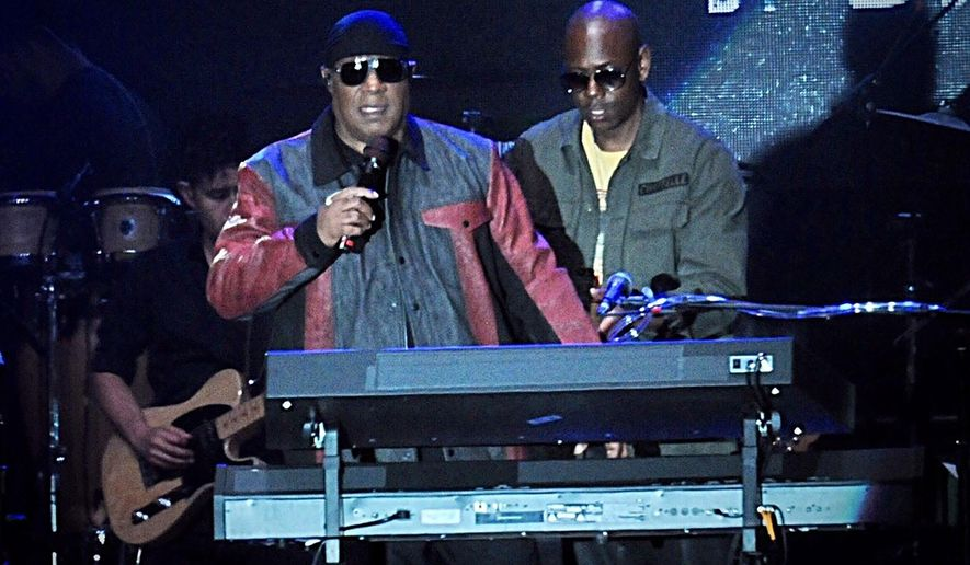 """Musician Stevie Wonder, front left, and comedian Dave Chappelle appear on stage during the """"Gem City Shine,"""" event in the Oregon District in Dayton, Ohio, Sunday, Aug. 25, 2019. Chappelle, who resides in nearby Yellow Springs, hosted the special block party and benefit concert for those affected by the recent mass shooting. (Marshall Gorby/Dayton Daily News via AP)"""