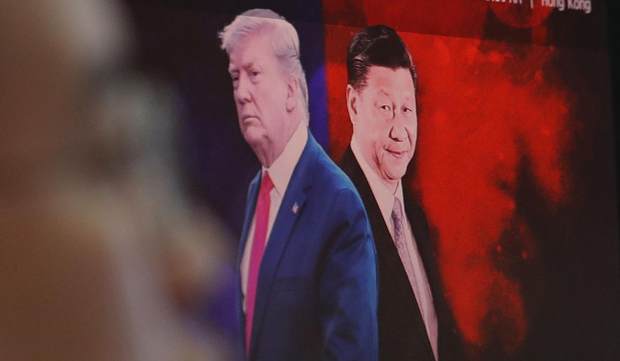 A computer screen shows images of Chinese President Xi Jinping, right, and U.S. President Donald Trump as a currency trader works at the foreign exchange dealing room of the KEB Hana Bank headquarters in Seoul, South Korea, Monday, Aug. 26, 2019. Asian shares tumbled Monday after the latest escalation in the U.S.-China trade war renewed uncertainties about global economies, as well as questions over what Trump might say next. (AP Photo/Ahn Young-joon)