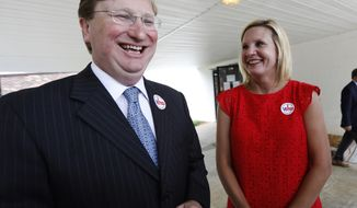 Lt. Gov. Tate Reeves, left, and his wife Elee Reeves share a laugh as he speaks with reporters about the final days of the runoff campaign for the GOP nomination for governor, Tuesday, Aug. 27, 2019, at his Flowood, Miss., voting precinct. Reeves has won the Republican nomination for governor and will face Democratic Attorney General Jim Hood and two other candidates in November. (AP Photo/Rogelio V. Solis)
