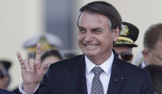 Brazils President Jair Bolsonaro makes a signal with his hand during a military ceremony for the Day of the Soldier, at Army Headquarters in Brasilia, Brazil, Friday, Aug. 23, 2019. Brazilian President Jair Bolsonaro says he's leaning toward sending the army to help fight Amazon fires that have alarmed people across the globe. (AP Photo/Eraldo Peres)