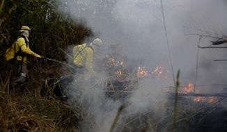 """Firefighters work to put out fires along the road to Jacunda National Forest, near the city of Porto Velho in the Vila Nova Samuel region that is part of Brazil's Amazon, Monday, Aug. 26, 2019. The Group of Seven nations on Monday pledged tens of millions of dollars to help Amazon countries fight raging wildfires, even as Brazilian President Jair Bolsonaro accused rich countries of treating the region like a """"colony."""" (AP Photo/Eraldo Peres)"""
