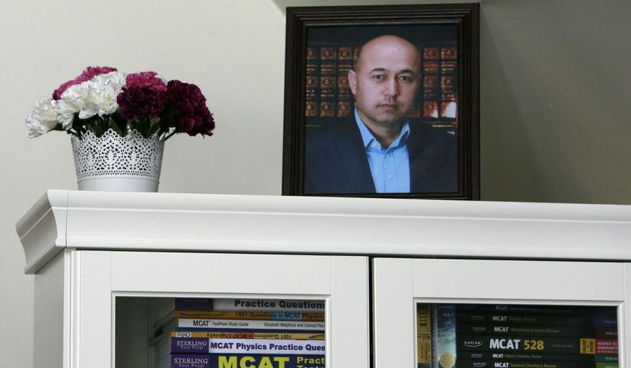 A portrait of Yalqun Rozi is seen atop a bookcase in his son and wife's apartment Thursday, April 18, 2019, in Philadelphia. For fifteen years, the literary critic had skillfully navigated state bureaucracies to publish textbooks that taught classic poems and folk tales to millions of his Turkic Uighur minority people in China's far western region of Xinjiang. (AP Photo/Jacqueline Larma)