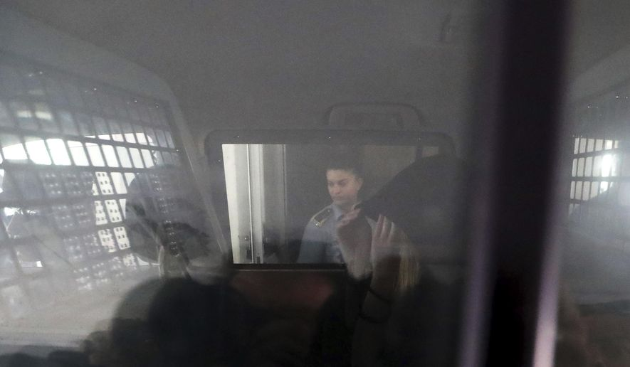 """A 19-year old British woman, is seen inside a police vehicle with head covered, as she leaves the Famagusta court in Paralimni, Cyprus, Tuesday, Aug. 27, 2019, after pleading not guilty to a public mischief charge.  The Cyprus court judge set the start of the trial for Oct. 2 and released the woman on bail, finding it """"proper and fair"""" to do so after having spent nearly two months in police detention. (AP Photo/Petros Karadjias)"""