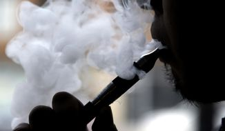In this April 23, 2014, photo, a man smokes an electronic cigarette in Chicago. (AP Photo/Nam Y. Huh) **FILE**