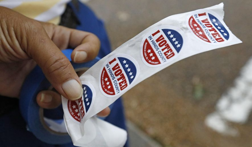 """Precinct 35 bailiff Herbert Broome, holds a strip of """"I Voted in Hinds County"""" stickers in his hand as he waits for voters to exit his north Jackson, Miss., precinct, Tuesday, Aug. 27, 2019. Featured among the runoff races are contests for the GOP's gubernatorial nomination and attorney general nomination. (AP Photo/Rogelio V. Solis)"""