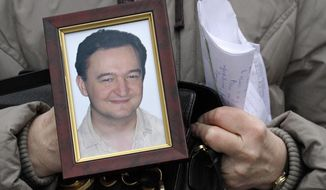 FILE - In this Nov. 30, 2009, file photo a portrait of lawyer Sergei Magnitsky, who died in jail, is held by his mother Nataliya Magnitskaya, as she speaks during an interview with the AP in Moscow. A top European court says Russia's failure to provide adequate medical care to jailed lawyer Sergei Magnitsky could have led to his 2009 death, which led to U.S. and European sanctions. The France-based European Court of Human Rights on Tuesday ordered Russia to pay Magnitsky's wife and mother 34,000 euros in damages. (AP Photo/Alexander Zemlianichenko, File)