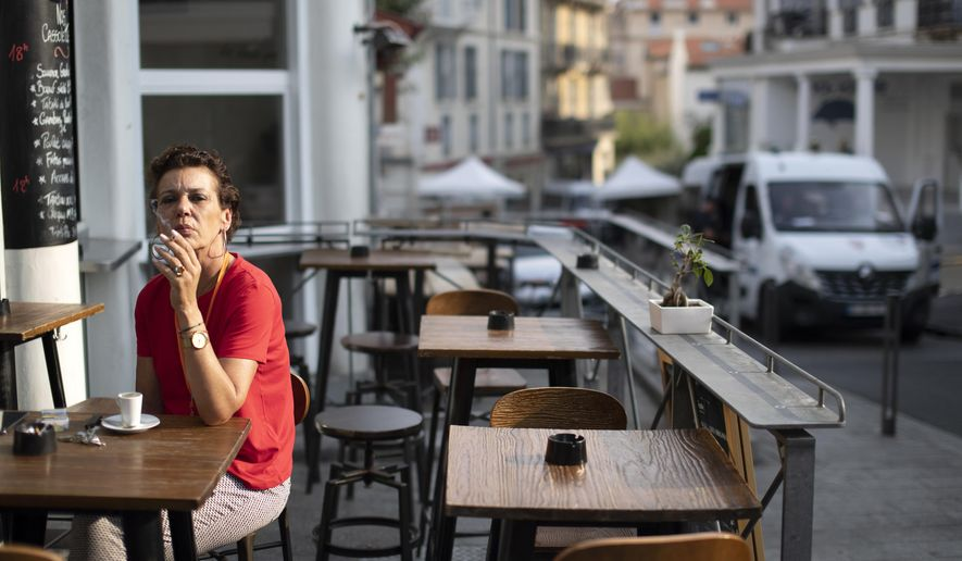 A woman has a cigarette with her morning coffee in Biarritz, France, on the third day of the G-7 summit, Monday, Aug. 26, 2019. France holds the 2019 presidency of the G-7, which also includes, the US, Britain, Canada, Germany, Italy and Japan. (AP Photo/Peter Dejong)