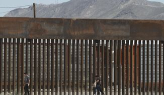 FILE - In this July 17, 2019, file photo, three migrants who had managed to evade the Mexican National Guard and cross the Rio Grande onto U.S. territory walk along a border wall set back from the geographical border, in El Paso, Texas, as seen from Ciudad Juarez, Mexico. The Department of Homeland Security is moving $271 million from other agencies such as FEMA and the U.S. Coast Guard to fund immigration detention beds and support its policy forcing asylum seekers to wait in Mexico.  (AP Photo/Christian Chavez, File)
