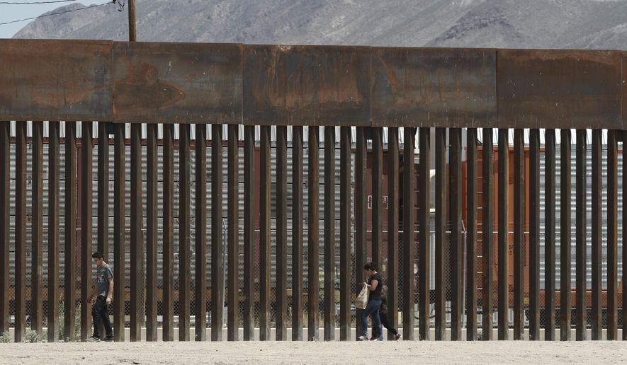 In this July 17, 2019, file photo, three migrants who had managed to evade the Mexican National Guard and cross the Rio Grande onto U.S. territory walk along a border wall set back from the geographical border, in El Paso, Texas, as seen from Ciudad Juarez, Mexico. (AP Photo/Christian Chavez, File)