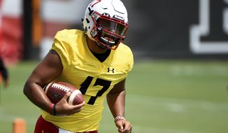 FILE - In this Aug. 2, 2019, file photo, Maryland quarterback Josh Jackson works out during an NCAA college football training camp in College Park, Md. With a new quarterback and a revamped playbook with an Alabama flair, Maryland's offense under first-year coach Michael Locksley has the potential to ring up plenty of points. (AP Photo/Will Newton, File)