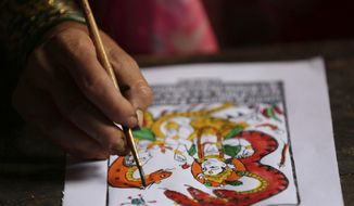 In this July 31, 2019, photo, Tej Kumari Chitrakar makes a traditional painting ahead of Naag Panchami festival at her residence in Bhaktapur, Nepal. Chitrakar families in the Nepalese capital of Kathmandu were renowned traditional painters and sculptors who depicted gods and goddesses on temples, masks of Hindu deities and posters for various religious celebrations. For Tej Kumari and her husband it is a struggle to keep the dying art alive against the modern mass produced prints. (AP Photo/Niranjan Shrestha)