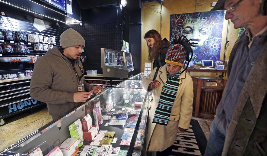 FILE - In this Jan. 4, 2018, file photo, cannabis consultant Juan Aguilar, left, assists customers Bill, right, and Nize Nylen and their son Russell shop for edible marijuana products in the Herban Legends pot shop in Seattle. Five years after Washington launched its pioneering legal marijuana market, officials are proposing their most ambitious overhaul yet of the way the industry is regulated, with plans for boosting minority ownership of pot businesses, spreading out oversight among a range of state agencies, and letting the smallest cannabis producers increase the size of the operations in an effort to help them become more competitive. (AP Photo/Elaine Thompson, File)