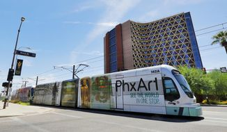 FILE - This Monday, Aug. 26, 2019 file photo shows a light rail train in downtown Tempe, Ariz., Monday, Aug. 26, 2019. Phoenix voters are weighing the future of mass rail transit in the nation's fifth largest city heading into the last day to cast ballots on a proposition asking whether any expansion of the light rail system should be permanently halted. Early mail-in ballots have already pushed overall turnout for Tuesday's special election higher than one held four years ago at the height of the Phoenix summer, when many people go on vacation to escape triple-digit temperatures. (AP Photo/Matt York, File)