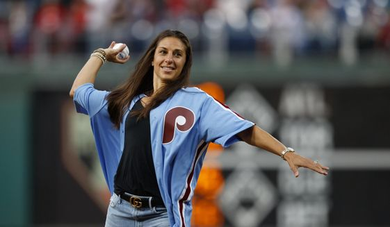 U.S. soccer player Carli Lloyd throws out a pitch before a baseball game between the Philadelphia Phillies and the Pittsburgh Pirates, Tuesday, Aug. 27, 2019, in Philadelphia. (AP Photo/Matt Slocum)