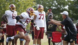 In this July 31, 2019, file photo, Washington Redskins offensive lineman, Hugh Thornton (69) runs drills as he is directed by offensive line coach Bill Callahan, right, during NFL football training camp in Richmond, Va. Now 27 months removed from a painful decision similar to what former teammate Andrew Luck made last week, Thornton is attempting to complete an NFL comeback with the Redskins that would be a major milestone in a lifelong journey full of adversity. (AP Photo/Steve Helber) ** FILE **
