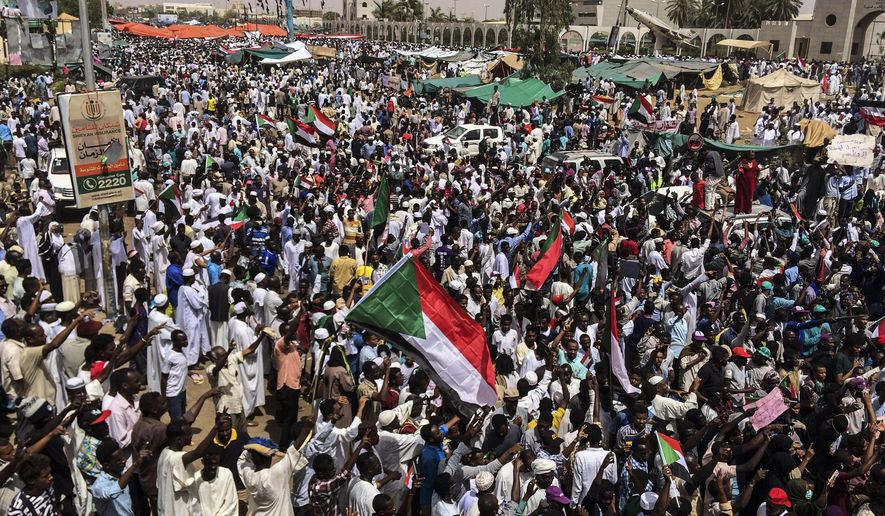 FILE - In this April 12, 2019 file photo, demonstrators rally in Sudan's capital, Khartoum. For the first time in three decades, Sudan has charted a path out of military rule following the formation of a power-sharing government by the pro-democracy movement and the generals who overthrew longtime autocrat Omar al-Bashir. But the fragile transition will be tested as leaders confront a daunting array of challenges. (AP Photo, File)