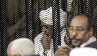 FILE - In this Saturday, Aug. 24, 2019 file photo, Sudan's autocratic former President Omar al-Bashir sits in a cage during his trial on corruption and money laundering charges, in Khartoum, Sudan. For the first time in three decades, Sudan has charted a path out of military rule following the formation of a power-sharing government by the pro-democracy movement and the generals who overthrew longtime autocrat Omar al-Bashir. (AP Photo, File)