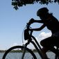 A girl on a bicycle pedals around the Tidal Basin with the Washington Monument in the background in Washington Monday, Aug. 17, 2015. Tourism officials say Washington drew a record 20.2 million visitors last year, with increases in international and domestic visitors. (AP Photo/Carolyn Kaster)
