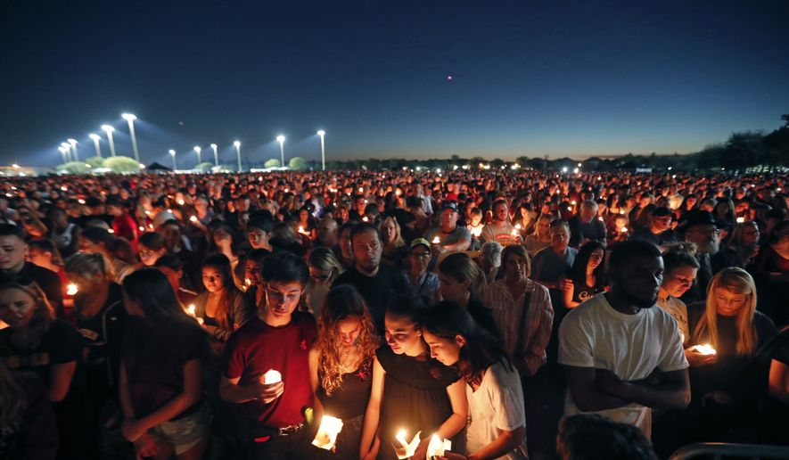 In this Feb. 15, 2018, file photo people attend a candlelight vigil for the victims of the shooting at Marjory Stoneman Douglas High School in Parkland, Fla. Parents whose children were killed or wounded during the Parkland high school massacre asked the Florida Supreme Court on Wednesday, Aug. 28, 2019, to rule that each pull of the trigger was a separate occurrence for which the Broward County School Board should be held liable. (AP Photo/Gerald Herbert, file) **FILE**