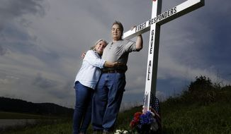 In this Aug. 6, 2019, file photo, Ansol and Janie Clark pose at a memorial Ansol Clark constructed near the Kingston Fossil Plant in Kingston, Tenn. The Tennessee Valley Authority was responsible for a massive coal ash spill at the plant in 2008 that covered a community and fouled rivers. The couple says the memorial is for the workers who have come down with illnesses, some fatal, including cancers of the lung, brain, blood and skin and chronic obstructive pulmonary disease. Ansol Clark drove a fuel truck for four years at the cleanup site, and now suffers from a rare blood cancer. (AP Photo/Mark Humphrey)