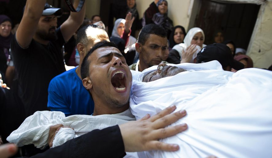 Mourners chant angry slogans as they carry the body of Palestinian Hamas police officer, Wael Khalifa, 45, in the family home, during his funeral in the Buriej refugee camp, central Gaza Strip, Wednesday, Aug. 28, 2019. Khalifa and two other Hamas police officers were killed in explosions that ripped through police checkpoints in Gaza City overnight, Hamas' interior ministry said. (AP Photo/Khalil Hamra)