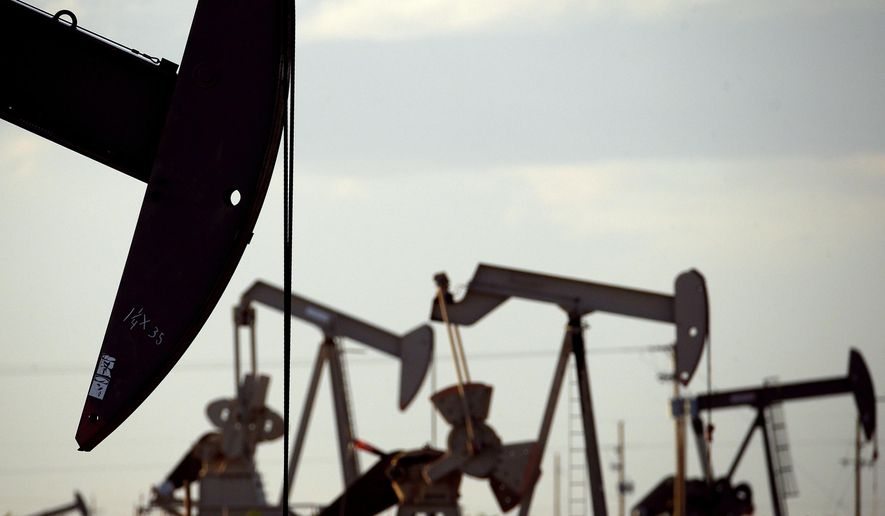 FILE - In this April 24, 2015, file photo, pumpjacks work in a field near Lovington, N.M. State economists on Friday, Aug. 23, 2019, revised upward forecasts for state government income amid surging oil and natural gas production in New Mexico, giving lawmakers greater leeway as they begin crafting a general fund spending plan for the coming fiscal year. Most of the windfall is linked to steadily growing oil and natural gas production focused in the Permian Basin that straddles the state line between New Mexico and Texas. (AP Photo/Charlie Riedel, File)