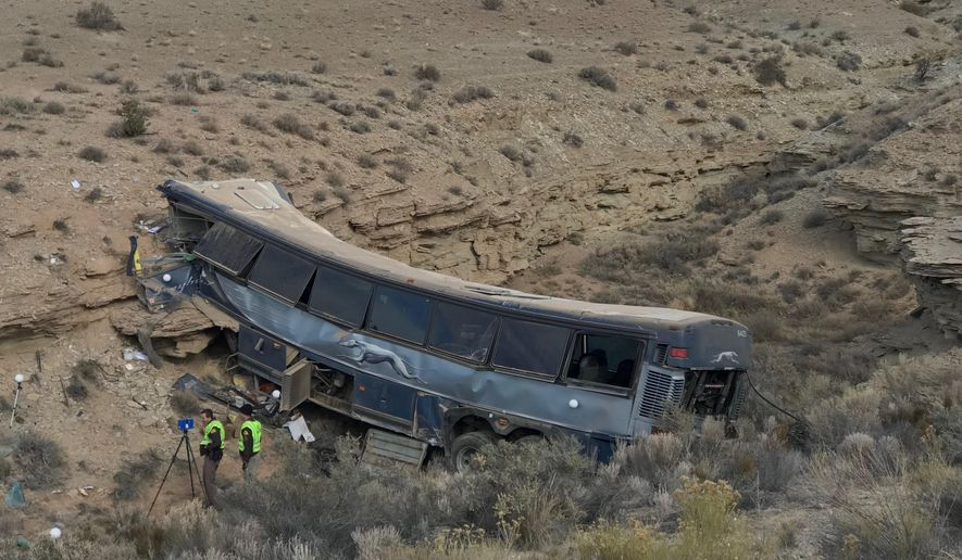 FILE - This Jan. 1, 2018, file photo, shows the aftermath of a Greyhound bus crash in Emery County, Utah. A second passenger has sued the Greyhound bus company and a driver who authorities say fell asleep before the bus careened off a road in the Utah desert two years ago, killing one person and injured 12 others. Clemente Velazquez of Rogers, Arkansas, says in a lawsuit filed in July that he's incurred more than $75,000 in damages from medical bills and lost wages after he suffered neck and back injuries and has been psychologically traumatized by the crash New Year's Eve 2017. (Ben Tidswell/The Deseret News via AP, File)