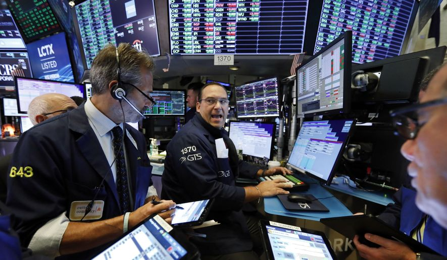 In this Aug. 21, 2019, file photo specialist Anthony Matesic, center, works with traders at his post on the floor of the New York Stock Exchange.   (AP Photo/Richard Drew, File)