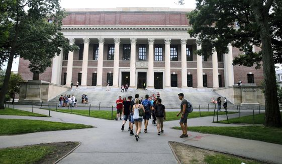 FILE - In this Aug. 13, 2019 file photo, students walk near the Widener Library in Harvard Yard at Harvard University in Cambridge, Mass. University and federal officials confirmed that incoming Harvard University student Ismail Ajjawi, 17, of Lebanon, was refused entry into the U.S. after landing at Logan International Airport in Boston on Friday, Aug. 23. (AP Photo/Charles Krupa, File)