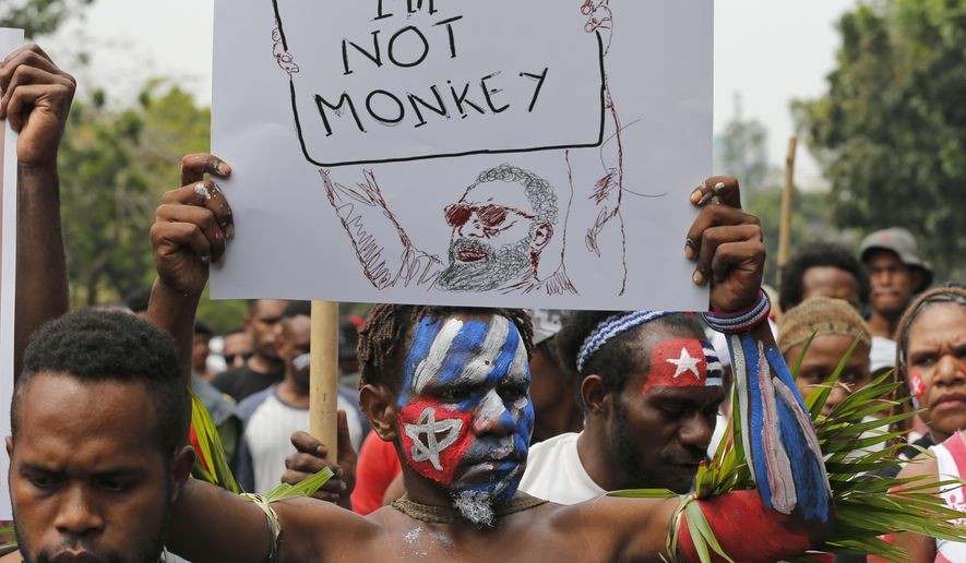 A Papuan students with faces painted with the colors of the separatist 'Morning Star' flag holds up a poster during a rally near the presidential palace in Jakarta, Indonesia, Wednesday, Aug. 28, 2019. A group of West Papuan students in Indonesia's capital staged the protest against racism and called for independence for their region. (AP Photo/Tatan Syuflana)