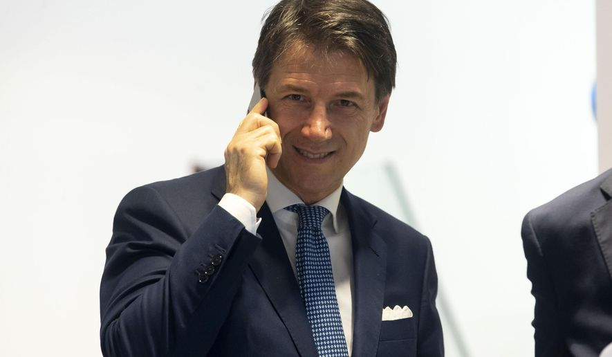 """Italy's Prime Minister, Giuseppe Conte, talks at the phone inside a mobile phones shop in the center of Rome, Tuesday, Aug. 27, 2019. While Italians don't know if they'll soon have a new government, let alone who would lead it, U.S. President Donald Trump has cast his vote -- for caretaker Premier Giuseppe Conte. A day after the two finished attending the G-7 summit in France, Trump tweeted on Tuesday that he hoped Conte would """"remain"""" as premier. (Massimo Percossi/ANSA via AP)"""