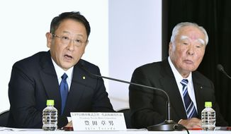 FILE - In this Oct. 12, 2016 file photo, Toyota Motor Corp. President Akio Toyoda, left, speaks with Suzuki Motor Corp. Chairman Osamu Suzuki during a news conference in Tokyo.  Japan's top automaker, Toyota, and smaller rival Suzuki announced Wednesday, Aug. 28, 2019, they are partnering in the development of self-driving car technology, as manufacturers around the world grapple with innovations in the industry.(Shigeyuki Inakuma/Kyodo News via AP, File)