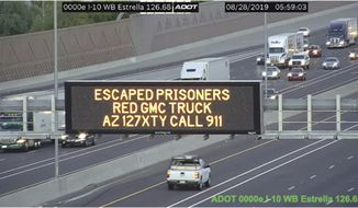 This photo from an Arizona Department of Transportation remote camera shows a digital sign  over Interstate 10 in the Phoenix metropolitan area that seeks the public's help in locating escaped murder suspects,Wednesday, Aug. 28, 2019. These signs on Arizona highways alert the public that a married couple suspected in a Tucson killing remained at large after overpowering two guards and escaping while being extradited from New York to Arizona. Tucson police said 56-year-old Blane Barksdale and 59-year-old wife Susan Barksdale escaped Monday evening in Blanding, Utah. (Arizona Department of Transportation via AP)