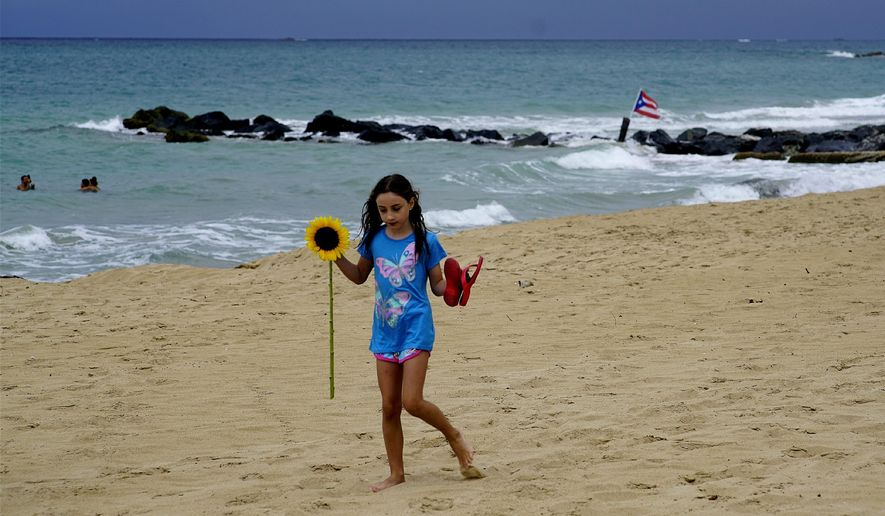 A girl walks on a sandy beach holding a sunflower and her flip-flops after the passing of Tropical Storm Dorian, in the Condado district of San Juan, Puerto Rico, Wednesday, Aug. 28, 2019. (AP Photo/Ramon Espinosa) ** FILE **