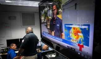 Emergency Center personnel stand next to a tv screen showing a meteorological image of Dorian, as they await its arrival, in Ceiba, Puerto Rico, Wednesday, Aug. 28, 2019. Puerto Rico is facing its first major test of emergency preparedness since the 2017 devastation of Hurricane Maria as Tropical Storm Dorian nears the U.S. territory at near-hurricane force.  (AP Photo/Ramon Espinosa)