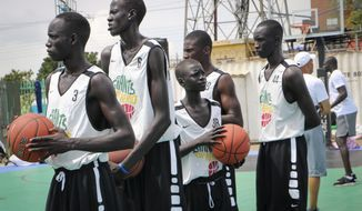 In this photo taken Tuesday, Aug. 20, 2019, players stand on the court doing exercises during a three-day basketball training camp run by Giants of Africa in Juba, South Sudan. Masai Ujiri, president of the Toronto Raptors basketball team who won the NBA championship for the first time this year, is founder of the Giants of Africa non-profit organization which runs a three-day training camp in South Sudan to empower youth through basketball. (AP Photo/Sam Mednick)