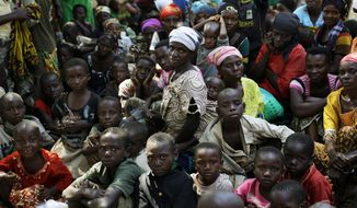 FILE - In this Saturday, May 23, 2015 file photo, refugees who fled Burundi's violence and political tension wait to board a UN ship, at Kagunga on Lake Tanganyika, Tanzania, to be taken to the port city of Kigoma. The United Nations refugee agency is urging the governments of Tanzania and Burundi not to forcibly repatriate Burundian refugees sheltering in Tanzania, after Tanzanian authorities said Tuesday, Aug. 27, 2019, that they had reached an agreement with Burundi to send all Burundian refugees back home from Oct. 1, 2019. (AP Photo/Jerome Delay, File)