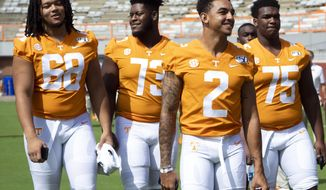 FILE - In this Aug. 4, 2019, file photo, Tennessee quarterback Jarrett Guarantano (2) and, from left, offensive linemen Marcus Tatum (68), Trey Smith (73) and Jerome Carvin (75) walk along the field during Tennessee's NCAA college football Fan Day and team photo shoot in Knoxville, Tenn. Tennessee coach Jeremy Pruitt announced Wednesday, Aug. 28, that  Smith has gained medical clearance to play this year and that defensive lineman Aubrey Solomon has received an NCAA waiver enabling the Michigan transfer to play for his new team immediately. (Saul Young/Knoxville News Sentinel via AP, File)