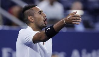 Nick Kyrgios, of Australia, points out distractions in the crowd during his match against Steve Johnson, of the United States, during the first round of the U.S. Open tennis tournament in New York, early Wednesday, Aug. 28, 2019. (AP Photo/Charles Krupa)