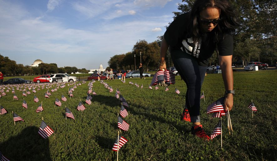 Patrice Sullivan, whose boyfriend, a Marine, died from suicide, helps to remove 5,000 small U.S. flags representing suicides of active and veteran members of the military line the National Mall, Wednesday, Oct. 3, 2018, in an action by the Iraq and Afghanistan Veterans of America (IAVA), in Washington. (AP Photo/Jacquelyn Martin)