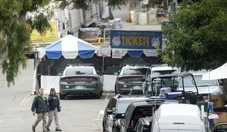 FILE - In this July 29, 2019, file photo, FBI personnel pass a ticket booth at the Gilroy Garlic Festival in Calif., the morning after a gunman killed multiple people and wounded over a dozen others. Gilroy police say they have identified an additional person who suffered a gunshot wound during a deadly shooting at a famous garlic festival last month. Authorities say a 58-year-old man sustained a graze wound to his head that required stitches. The man's injuries bring the total number of people shot during the July 28 shooting to 17. (AP Photo/Noah Berger, File)