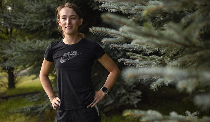 This Aug. 15, 2019 photo shows University of Montana cross country runner June Eastwood posing for a photo at Campbell Park in Missoula, Mont. Eastwood is set to be the first transgender athlete to compete in NCAA Division I cross-country. Eastwood competed for the UM men's track and cross country teams from 2016 to 2018. After a year of taking testosterone suppressants and estrogen pills, Eastwood meets the NCAA requirements to compete on the UM women's team. (Rachel Leathe/Bozeman Daily Chronicle via AP)