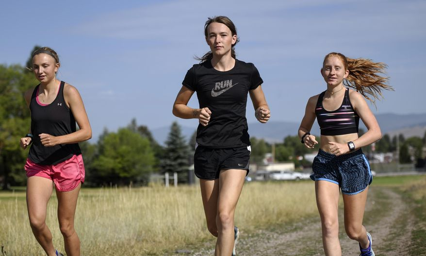 In this Aug. 15, 2019, file photo, University of Montana cross country runner June Eastwood, center, warms up with her teammates at Campbell Park in Missoula, Mont. (Rachel Leathe/Bozeman Daily Chronicle via AP) ** FILE **