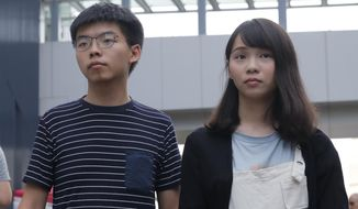 In this June 18, 2019, file photo, pro-democracy activists Agnes Chow, right, and Joshua Wong meet media outside a government office in Hong Kong. Demosisto, a pro-democracy group in Hong Kong posted on its social media accounts that well-known activist Joshua Wong had been pushed into a private car around 7:30 a.m. Friday, Aug. 30, 2019, and was taken to police headquarters. It later said another member, Agnes Chow, had been arrested as well. (AP Photo/Kin Cheung)