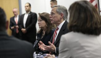 Texas Governor Greg Abbott sits with families of victims and survivors of the Aug. 3 shooting at Walmart in El Paso, Texas, Thursday, Aug. 29, 2019. About 30 representatives from law enforcement and non governmental agencies were on the roundtable discussion of public safety. (Mark Lambie/The El Paso Times via AP)