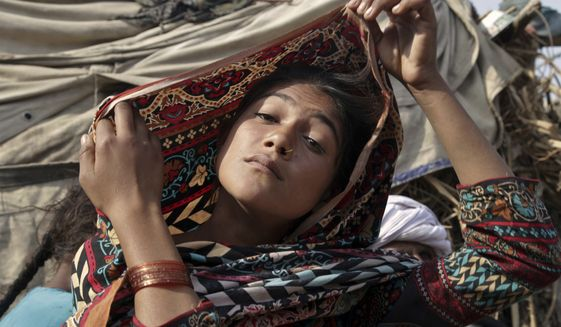 In this Tuesday, Dec. 20, 2016, file photo, Saima, who married an older man in her early teens, fixes her scarf during an interview in Jampur, Pakistan. (AP Photo/K.M. Chaudhry) ** FILE **